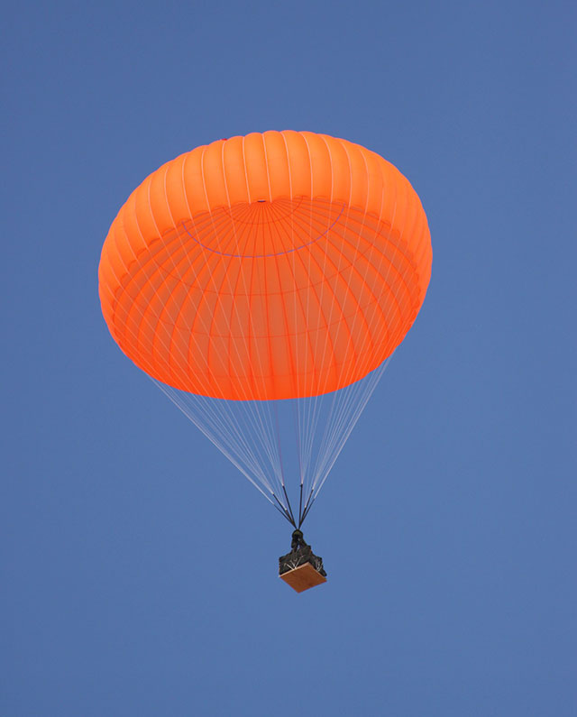 Cargo drop with orange parachute