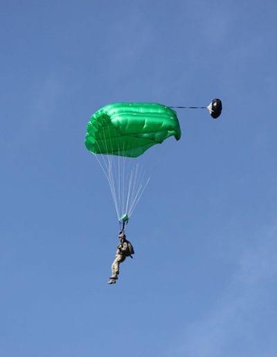 Man descending in a green seven cell Falcon parachute