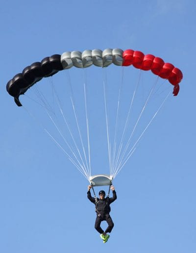 Man descending in a red white and blue nine cell Falcon parachute