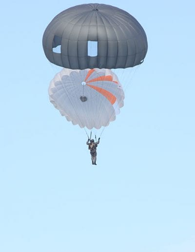 Man descending with double canopies deployed