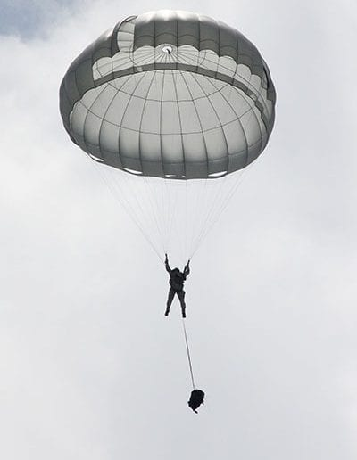 Man descending in an Invasion II parachute with separated bag
