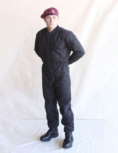 Man posing in black jumpsuit wearing a beret