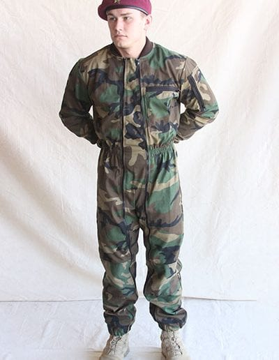 Man posing in camouflage jumpsuit wearing a beret